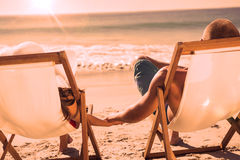 Cute couple holding hands while lying on their deck chairs. Cute couple on the beach holding hands while lying on their deck chairs Stock Photo