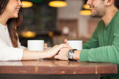 Cute couple holding hands in a restaurant Stock Image