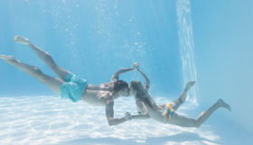 Cute couple holding hands underwater in the swimming pool Stock Images