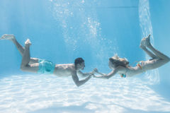 Cute couple holding hands underwater in the swimming pool Royalty Free Stock Photo