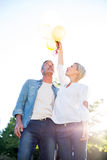 Cute couple holding up balloons at the park Stock Photography