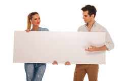 Cute couple holding a white blank sign in studio royalty free stock photos
