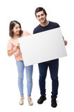 Cute couple holding a white sign. Full length portrait of a young couple holding a white sign while one of them looks at it in a studio Royalty Free Stock Photography