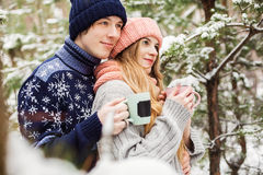 Cute couple with hot tea in cups in forest among fir trees Royalty Free Stock Image