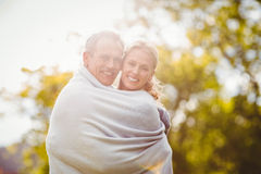 Cute couple hugging with a blanket around Stock Photo