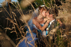Cute couple is hugging and kissing in the herbs on the backgroun Stock Photography