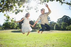 Cute couple jumping in the park together holding hands Royalty Free Stock Image
