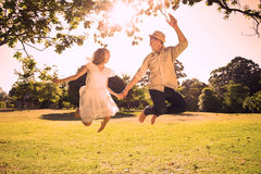Cute couple jumping in the park together holding hands Stock Images