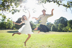 Cute couple jumping in the park together Stock Photo
