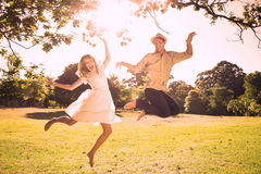 Cute couple jumping in the park together Stock Photos