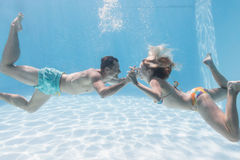 Cute couple kissing underwater in the swimming pool Stock Photo