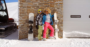Cute couple leaning against ski resort garage Stock Photo