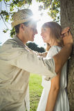Cute couple leaning against tree in the park Stock Images