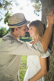 Cute couple leaning against tree in the park Royalty Free Stock Image