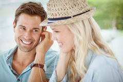 Cute couple listening to music together in cafe stock image