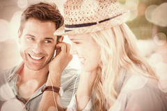 Cute couple listening to music together in cafe. On a sunny day in the city Stock Photo