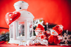 Cute couple of little snowmen is standing near the white fairy lantern with a toy heart on it and decorated fir tree branch. Stock Photography