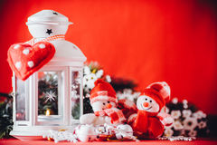 Cute couple of little snowmen is standing near the white fairy lantern with a toy heart on it and decorated fir tree branch. Royalty Free Stock Image