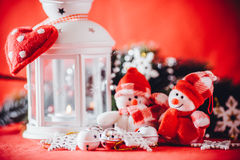 Cute couple of little snowmen is standing near the white fairy lantern with a toy heart on it and decorated fir tree branch. Stock Image
