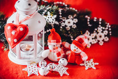 Cute couple of little snowmen is standing near the white fairy lantern with a toy heart on it and decorated fir tree branch. Royalty Free Stock Images
