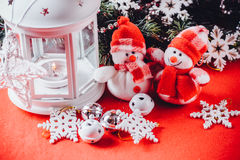 Cute couple of little snowmen is standing near the white fairy lantern with a toy heart on it and decorated fir tree branch. Stock Images