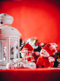 Cute couple of little snowmen is standing near the white fairy lantern with a toy heart on it and decorated fir tree branch. Stock Photo