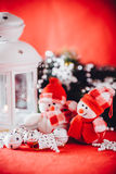Cute couple of little snowmen is standing near the white fairy lantern with a toy heart on it and decorated fir tree branch. Stock Photos