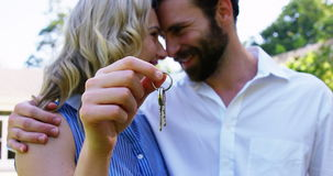 Cute couple looking each other and holding keys. On a sunny day stock video footage