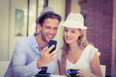Cute couple looking at a smartphone Royalty Free Stock Image
