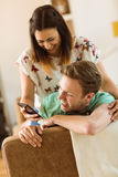Cute couple looking at smartphone on couch Royalty Free Stock Photo