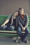 Cute couple in love. Young trendy couple sitting together on bench looking at camera in love Stock Photo
