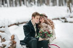 Cute couple in love with a bouquet are sitting on the log on background of the winter forest. Artwork royalty free stock image
