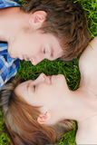 Cute couple in love embracing lying outdoors stock image