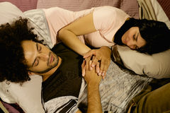 Cute couple in love sleeping in bed holding hands Stock Photos