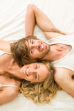 Cute couple lying in bed and looking at camera Royalty Free Stock Image