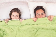 Cute couple lying in bed under the covers. Cute couple lying in bed smiling under the covers royalty free stock image