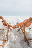Cute couple lying on deck chairs Royalty Free Stock Image