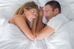 Cute couple lying and looking at each other in bed Stock Photo