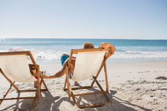 Cute couple lying on their deck chairs royalty free stock images