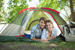 Cute couple lying in their tent smiling at camera Stock Images