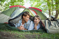 Cute couple lying in their tent smiling at each other Stock Photo