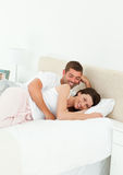 Cute couple lying together on their bed Stock Image