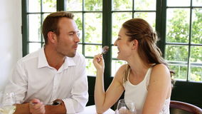 Cute couple making each other taste their deserts. In a restaurant stock video