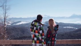 Cute couple in multicolored ski suits standing on the observation deck and looking on gorgeous mountains. Romantic stock video