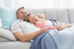 Cute couple napping under a blanket on the couch Royalty Free Stock Photos