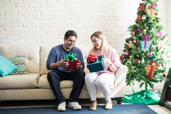 Cute couple opening Christmas presents. Full length view of a young Hispanic couple opening some Christmas presents while sitting next to their tree at home Stock Photos