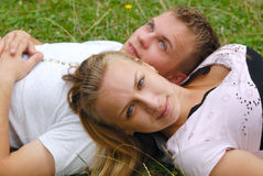 Cute couple outdoor. Young couple laying on the grass Stock Photography