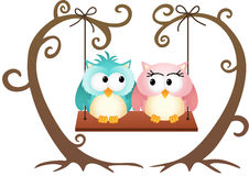 Cute couple owls in love on a swing Stock Photo