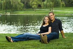 Cute Couple at the Park. Cute couple sitting by the lake at the park Stock Photos