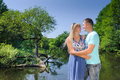 Cute couple in the park on a sunny day. Beautiful happy mature couple hugging near river waterfall at summer day. Happy guy and girl Stock Photo
